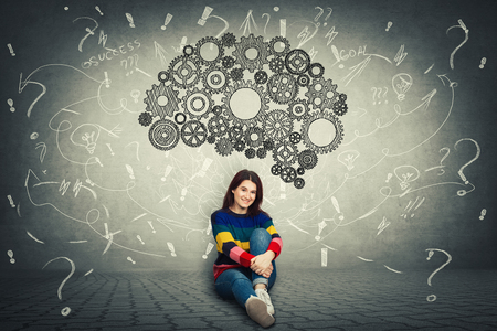 Pretty casual woman sitting on the floor and a huge gear brain above her head, positive thinking, question marks and mess as thoughts around. Concept for mental, psychological development. Stock Photo