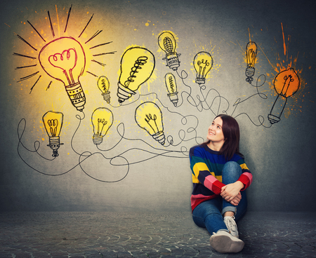 Young woman sitting on the floor smiling looking at bright lightbulbs on the wall. Smart and ingenious girl has a different thinking, genius creativity concept, alternative idea as the way to success. Stok Fotoğraf