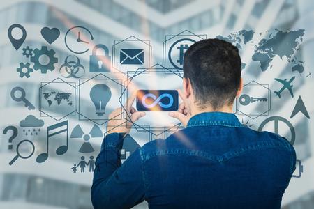 Vue arrière du jeune homme tenant un téléphone portable sur les technologies multimédias d'interface numérique avec le symbole de l'infini à l'écran. Concept de communication et de mise en réseau mondial moderne. Services commerciaux virtuels.