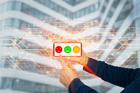 Man hands holding a smartphone touch the screen to choose feedback. Press on sad face emoticon. Customer service rating concept. Unsatisfied client, virtual business services efficiency management.
