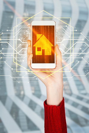 Woman hand raised up holding a mobile phone showing touch screen digital interface with golden house icon, search best home place. Modern technology, property insurance concept. 免版税图像