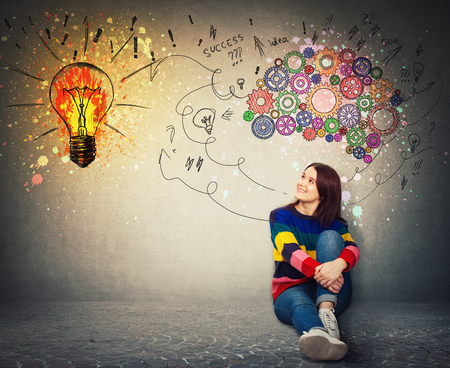 Young woman sitting on the floor smiling looking at a bright light bulb on the wall. Idea concept, creative thinking as colorful gear brain above head, create a genius. Mental development symbol.