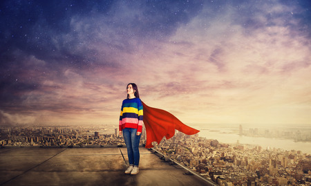 Confident woman standing on skyscraper rooftop over big city sunset horizon as a superhero with a red cape watching the cityscape horizon. Super power metaphor.