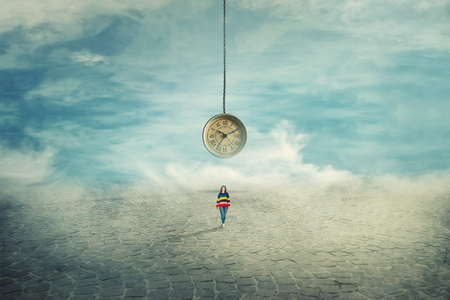 Surreal view as a woman walking on a pavement road and a suspended clock on her back hanging from the sky. The importance of time in the modern world. Time travel concept. Banque d'images - 115945922