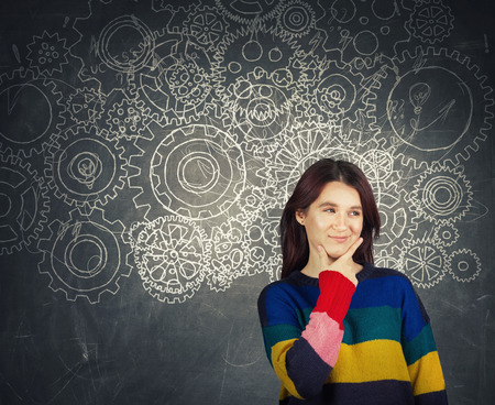 Hard thinking serious smart woman holding hand under chin over blackboard background gear brain arrows and mess as thoughts. Concept for mental, psychological development. Finding solution to problem. Stock Photo