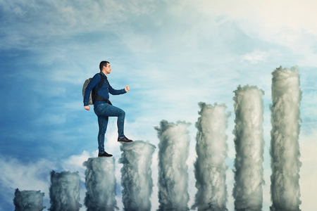 Confident man climb up to the top of a graph made of clouds over blue sky background. No limits growing success concept, business metaphor as keep on moving forward.