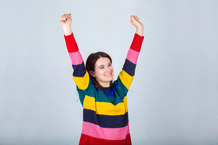Cheerful young woman celebrating victory as raising hands up sign of success.