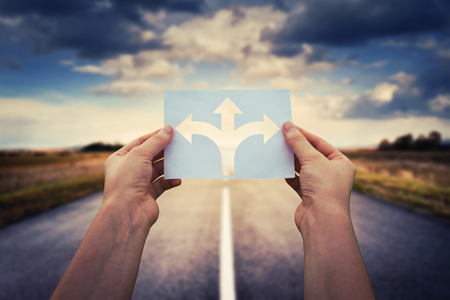 Hands holding paper with arrows crossroad symbol splitted in three different directions. Choose the correct way between left, right and front. Difficult decision concept, over asphalt road background.