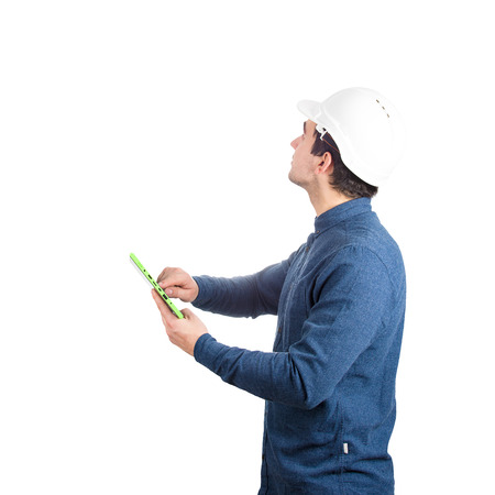 Serious confident young man engineer wearing protective helmet holding a pc tablet gadget looking up isolated over white background.