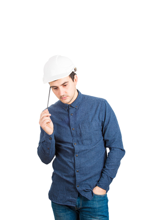 Thoughtful young man engineer wearing protective helmet thinking pointing pencil to head isolated over white background with copy space.