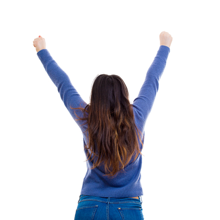 Freedom concept rear view of casual young woman student raising hands up wide opened celebrating success isolated over white background.