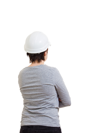Rear view of young woman engineer wearing protective helmet isolated over white background. Stock Photo