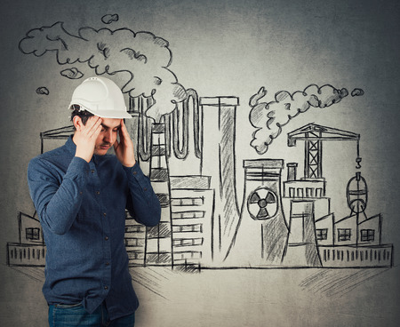 Stressed young man engineer industry worker holding arms to head feeling exhausted. Headache and health problems. Toxic factory sketch, nuclear plants emit smoke. Dirty, contaminated air pollution.