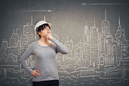 Ingenious young woman engineer wearing protective helmet holding hand under chin looking up thinking of new ideas over an imaginary drawn city background.