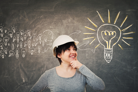 Ingenious young woman engineer wearing protective helmet holding hand under chin looking up thinking. Concept of gathering ideas into a big lightbulb. Imagens - 116321840
