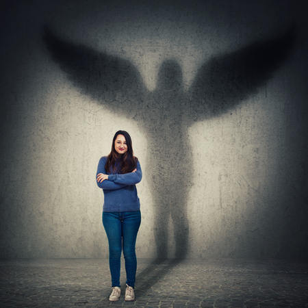 Casual young woman student full length portrait holding arms crossed confident looking as casting a hero shadow with angel wings on a dark room wall. Inner strength, ambition and leadership concept.