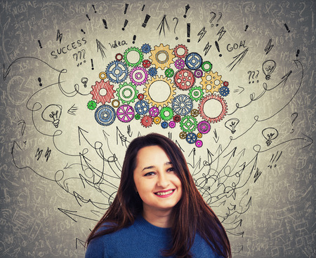 Close up portrait of a young woman with colorful cogwheel brain above head. Happy emotion, positive thinking with arrows and curves mess as thoughts. Concept for mental, psychological development.