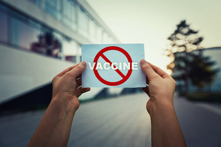 Hands holding a paper sheet with red restriction sign and word vaccine. Refuse vaccination due to possible health problems. Say no to fake immunisation against viruses. Laboratory building background.