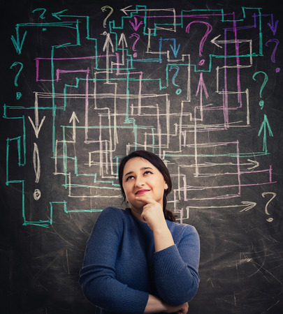 Puzzled young woman in front of blackboard with different colorful arrows try to solve a question maze and find the answer. Problem analysis solution concept with exclamation and interrogation marks.