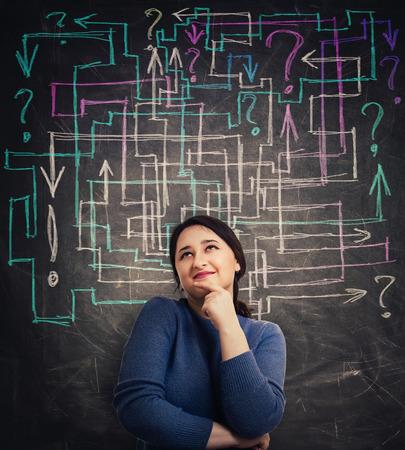 Une jeune femme perplexe devant un tableau noir avec différentes flèches colorées essaie de résoudre un labyrinthe de questions et de trouver la réponse. Concept de solution d'analyse de problème avec points d'exclamation et d'interrogation.