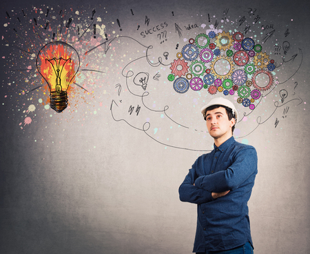 Confident man engineer wearing protective helmet, hands crossed over gray wall. Idea concept, creative thinking as colorful gear brain above head, create a genius. Mental development lightbulb symbol. Stock Photo