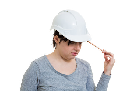 Thoughtful young woman engineer wearing protective helmet thinking pointing pencil to head isolated over white background with copy space.
