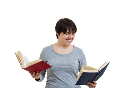 Doubtful young woman student or teacher holding two open books one red and another blue, choosing which one to read. Difficult decision, making the right choice, education concept.