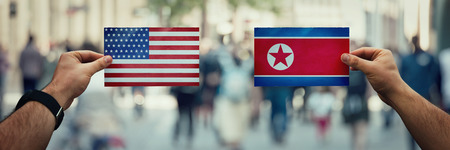 Two hands holding different flags, USA vs North Korea Republic on politics arena over crowded street background. Future strategy, relations between countries. Cooperation or opposite conflict concept. Stock Photo