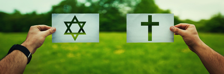 Religion conflicts as global issue concept. Two hands holding different faith symbols, Judaism vs Christianity belief over green field nature. Relations between different people doctrines and cult. Banco de Imagens