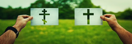 Religion conflicts as global issue concept. Two hands holding different Christianity cross symbols, Orthodox vs Catholic belief over green field nature. Relations between different people church faith