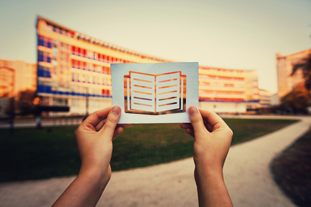 Hand holding a paper with books icon over university background. Lack of education global issue, students dont attend or are not enrolled in school. Inequality, marginalization and poverty problems. Stock Photo