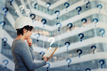 Puzzled woman engineer wearing protective helmet using tablet computer gadget looking thoughtful to get answer to many questions. Science searching and interrogation virtual marks. Modern technology. 版權商用圖片