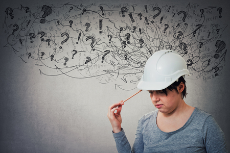 Thoughtful young woman engineer wearing protective helmet thinking pointing pencil to head, stressed looking down feeling exhausted. Headache, anxiety and health problems as sketch mess in his head.