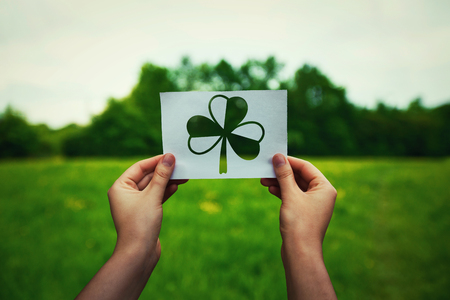 St. Patricks day, lucky charms as human hands holding a paper sheet with clover symbol over a green field nature background. Spring irish holiday celebration, shamrock icon. 免版税图像
