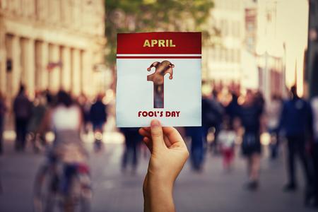 Mano che tiene una pagina del calendario con il simbolo del 1 pesce d'aprile su sfondo strada affollata. Vacanza internazionale di divertimento. Archivio Fotografico