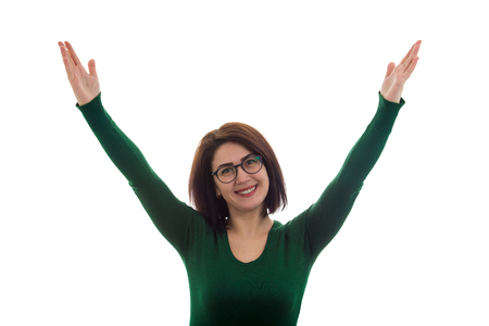 Cheerful young woman celebrating success, raising hands up isolated over white background.