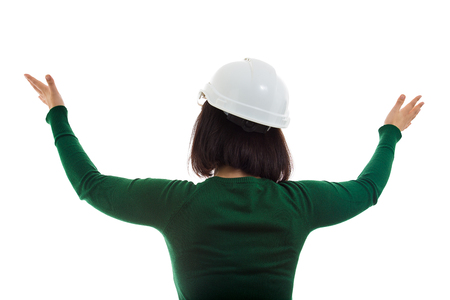 Rear view of young woman engineer gesturing and raising hands up wide opened. Worker wearing protective helmet isolated over white background.
