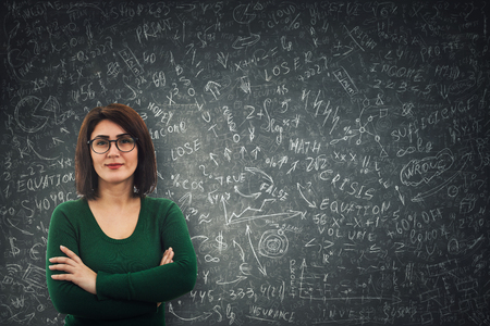 Confident businesswoman wearing glasses standing in front of a blackboard solving hard mathematics calculation, economics formula and equations Banco de Imagens - 119429383