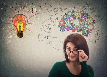 Serious businesswoman fixing glasses, great idea concept, creative thinking as colorful gear brain above head, create a genius