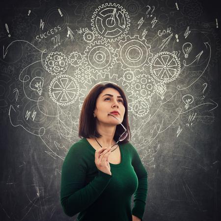 Une femme intelligente médite en levant en pensant à de nouvelles idées devant le tableau noir comme des roues dentées, des flèches et du désordre dessinés comme des pensées autour de la tête