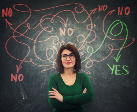 Pleasant casual young woman in front of a blackboard finding correct answer to her questions as curves arrows leaving head, leading to yes or no response Stock Photo