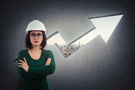 Woman engineer, wearing protective helmet, holding arms crossed, thoughtful looking over a rising graph arrow shape as a hole in concrete wall with a view to the city Imagens