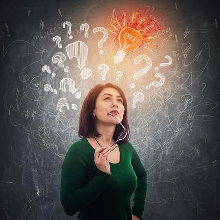 Une femme intelligente médite en levant en pensant à de nouvelles idées devant le tableau noir alors que des points d'interrogation, des ampoules et des flèches flottent au-dessus de la tête Banque d'images