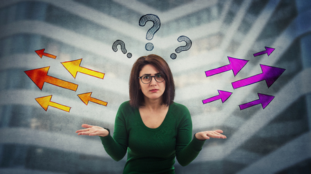 Perplexed woman with puzzled face confused and frustrated has to choose arrow direction, left or right side, question marks above head