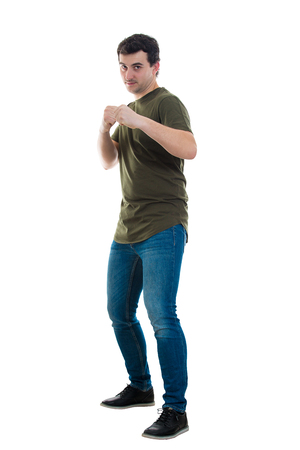 Full length portrait of casual angry young man ready for battle standing in fighting position isolated over white background. People self defense, strength and motivation concept, fight your fears.