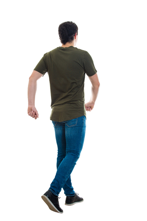 Full length rear view of casual young man confident fast walking isolated over white background. Motion shot making a step going ahead hurried.