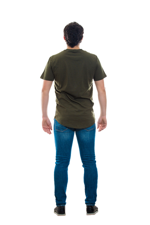 Full length rear view of casual young man standing relaxed looking ahead isolated over white background. Backside male body . Stock Photo