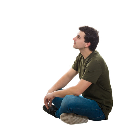 Side view handsome young man wearing casual jeans and t-shirt, sitting relaxed on the floor with crossed legs, looking thoughtful away isolated over white