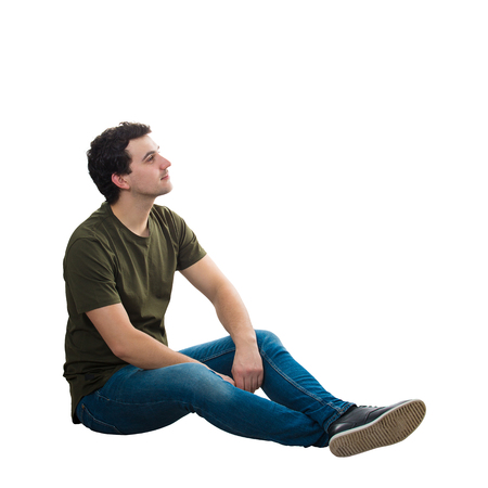 Side view handsome young man wearing casual jeans and t-shirt, sitting relaxed on the floor, looking thoughtful away, isolated over white