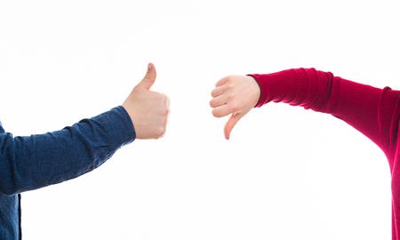 Cerca de las manos del hombre y la mujer dando pulgares hacia arriba y hacia abajo, gesto positivo vs negativo aislado en blanco